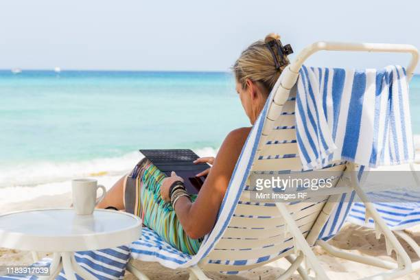 adult woman executive using smart phone on the beach - west indies stock pictures, royalty-free photos & images