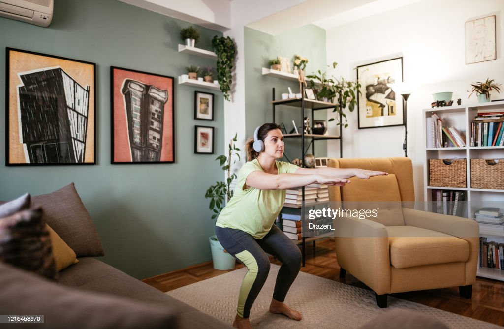 Adult woman exercising at home during quarantine - crouching and strength exercises : Stock Photo