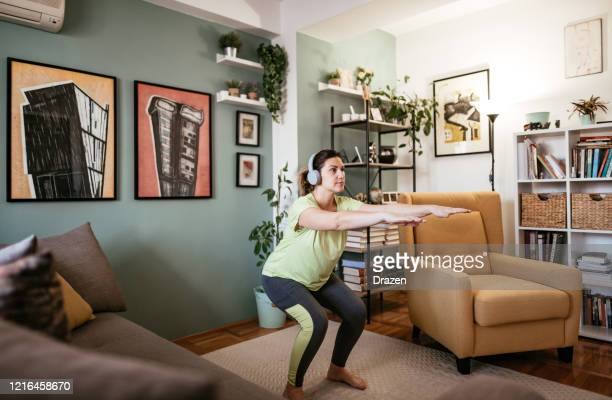 adult woman exercising at home during quarantine - crouching and strength exercises - squatting position stock pictures, royalty-free photos & images
