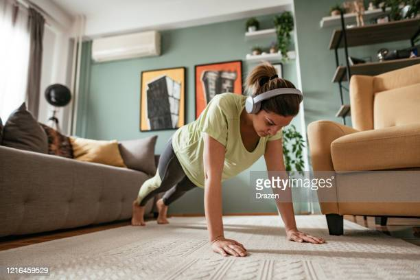 adult woman exercising at home during quarantine, doing push ups - push ups stock pictures, royalty-free photos & images