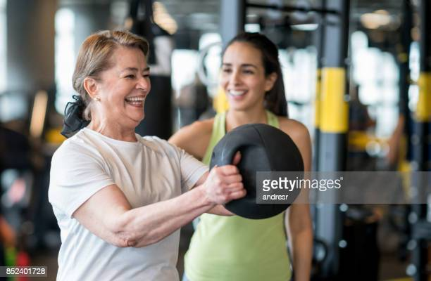 adult woman exercising at the gym with a personal trainer - weight stock pictures, royalty-free photos & images