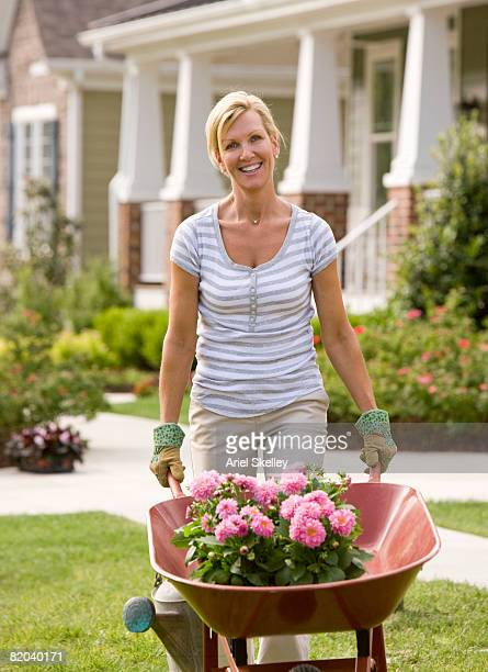 adult woman gardening in front of home - wheelbarrow stock pictures, royalty-free photos & images