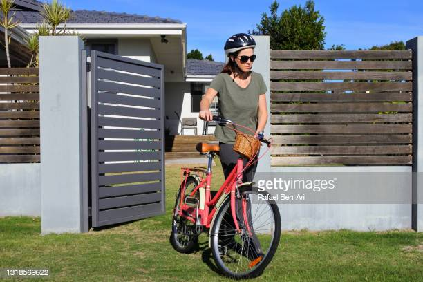 adult  woman going for a bike ride - rafael ben ari stock-fotos und bilder