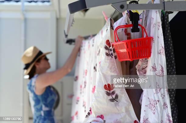 adult woman hanging laundry on washing line - rafael ben ari bildbanksfoton och bilder
