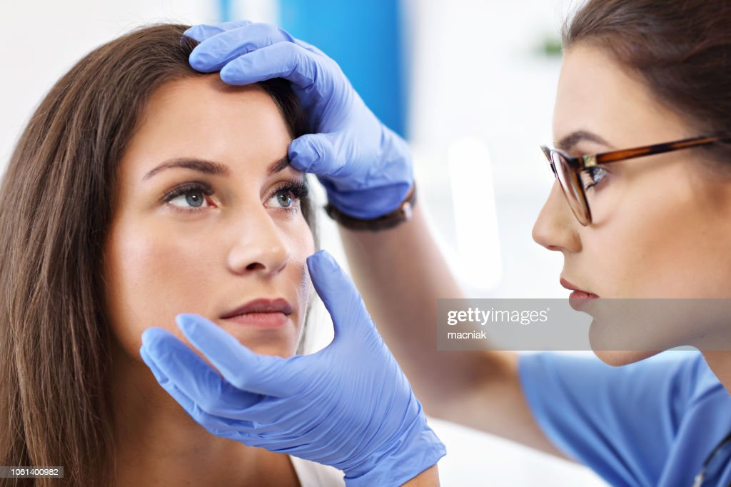 Adult woman having a visit at female oculist's office : Stock Photo