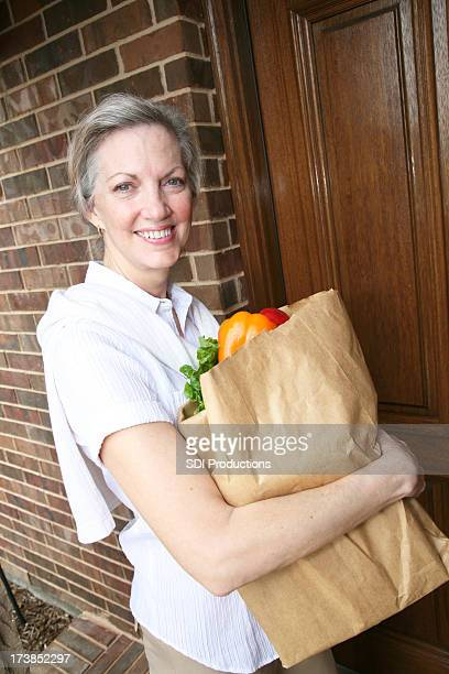 Adult Woman Holding Grocery Bag At Her Front Door