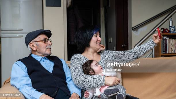 Adult Woman Holding Her Baby Girl And Taking Selfie With Grandfather