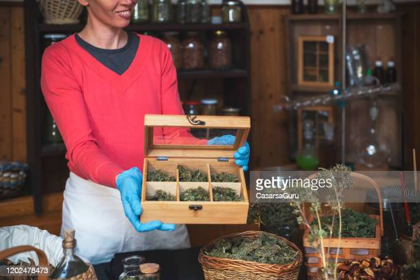 adult woman holding open box with different cannabis strains in her homeopathic medicine store - stock photo - cannabis store stock pictures, royalty-free photos & images