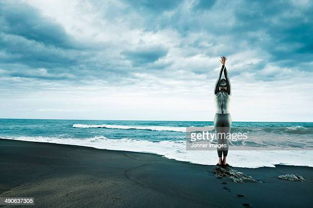 adult woman in wetsuit at beach - atmospheric mood stock pictures, royalty-free photos & images
