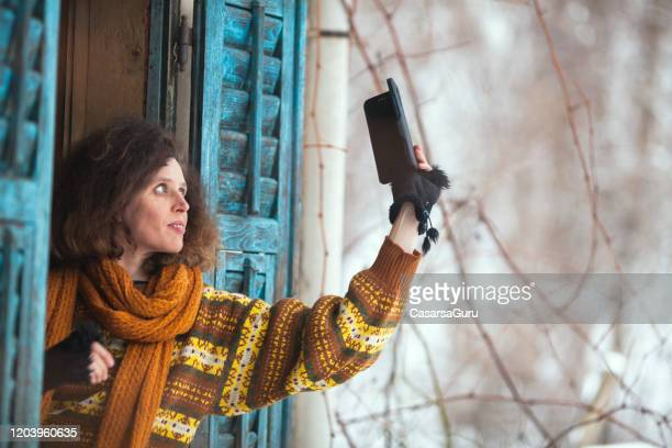 adult woman leaning out window holding her smart phone - stock photo - radio wave stock pictures, royalty-free photos & images