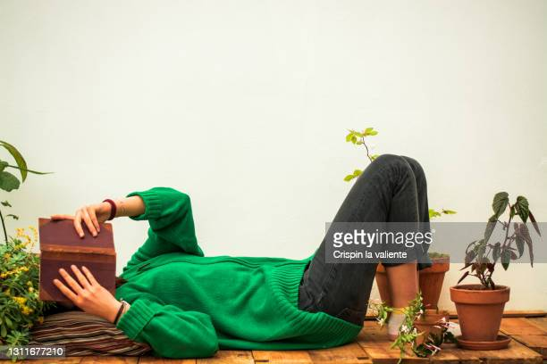adult woman lying on the wooden floor reading a book - obscured face stock pictures, royalty-free photos & images