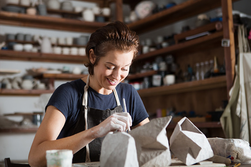 adult woman make pottery at table in workshop 1080224076