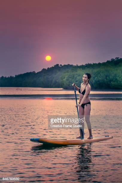Adult woman paddling on a board  mangrove swamp