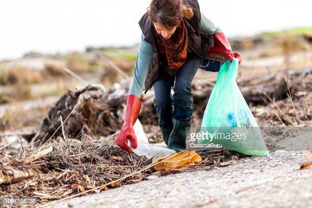 adult woman picking up trash in rural scene - picking up stock pictures, royalty-free photos & images