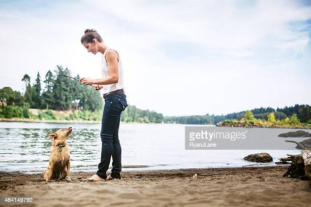 adult woman playing fetch with pet dog - willamette river stock photos and pictures