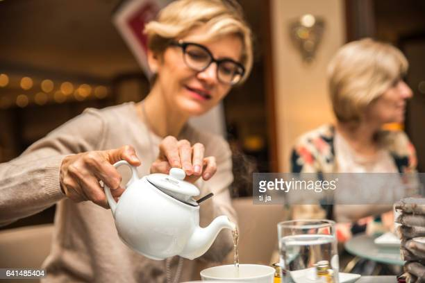 Adult woman pouring a tea in a cup