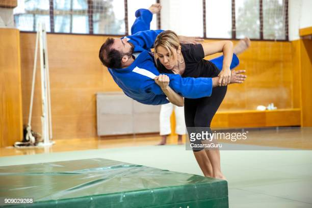 adult woman practicing self defense with judo trainer - judo stock photos and pictures