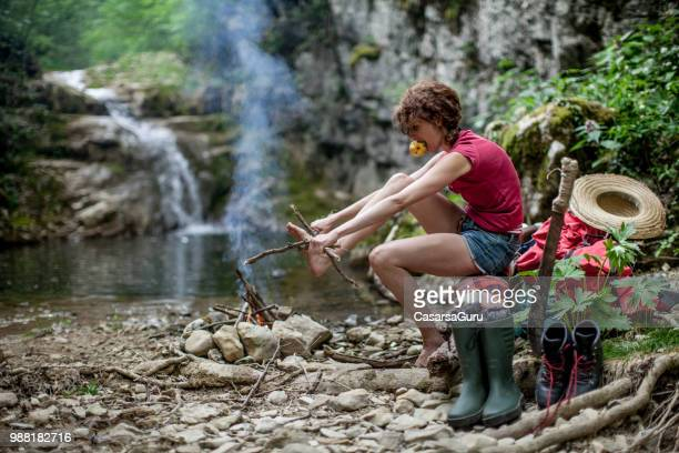 adult woman preparing and breaking firewood in campsite - survival stock pictures, royalty-free photos & images