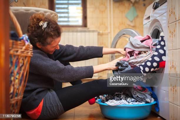 erwachsene frau zieht stuck-kleidung aus waschmaschine - frau gefesselt stock-fotos und bilder