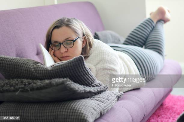 Adult woman reading a book on the purple sofa