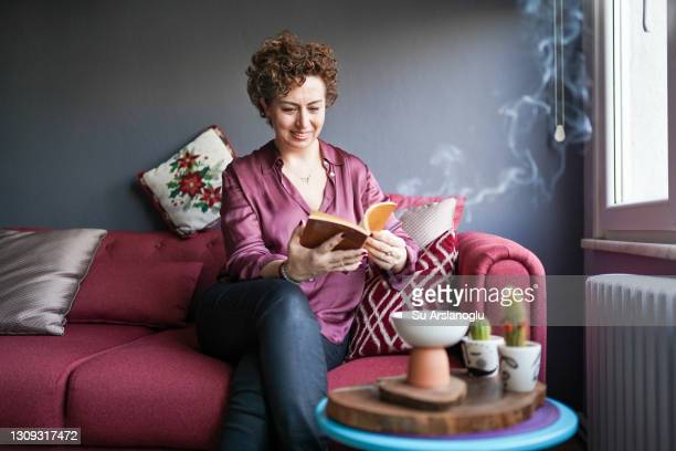 adult woman reading a book while incense is burning - incense coils stock pictures, royalty-free photos & images