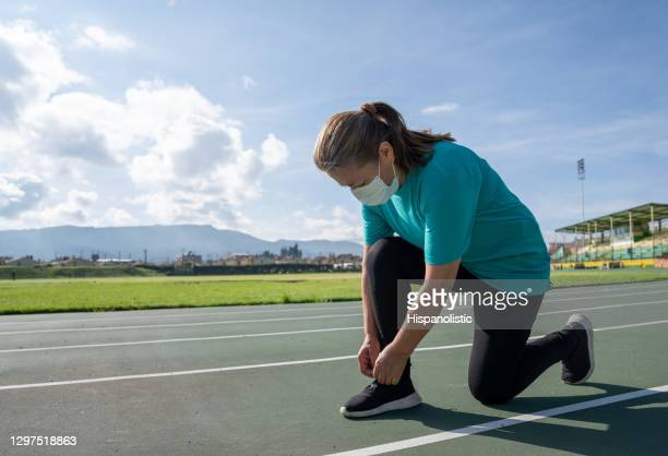 adult woman running at the track and tying her shoes while wearing a facemask - athletics stock pictures, royalty-free photos & images