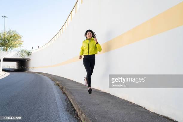 Adult Woman Running On Urban Street