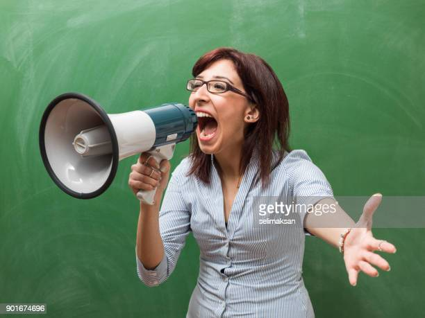 Adult Woman Shouting Through Megaphone In Front Of Green Chalkboard