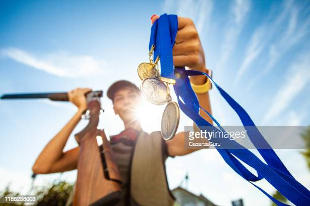adult woman showing medals and holding a rifle outdoors - second place stock pictures, royalty-free photos & images