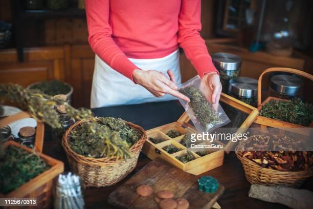 大人の女を示すパック乾燥大麻の植物の部分 - カンナビスサティバ ストックフォトと画像