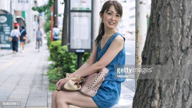 大人の女性がバス停で座っていると、朝の笑顔