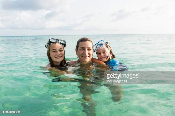 adult woman standing in ocean water at sunset with her children - sea swimming stock pictures, royalty-free photos & images