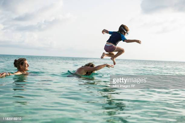 adult woman standing in ocean water at sunset with her children - sea swimming stock photos and pictures