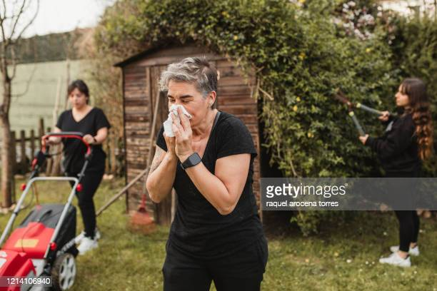 adult woman suffering from spring allergy and blowing a runny nose with a tissue while working in the garden - mucus stock pictures, royalty-free photos & images
