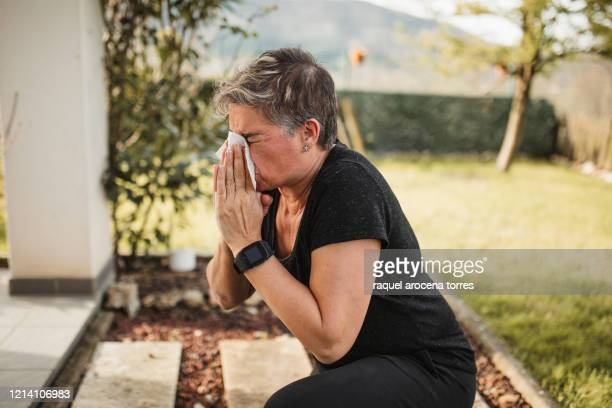 adult woman suffering from spring allergy and blowing a runny nose with a tissue while working in the garden - nasal mucus stock pictures, royalty-free photos & images
