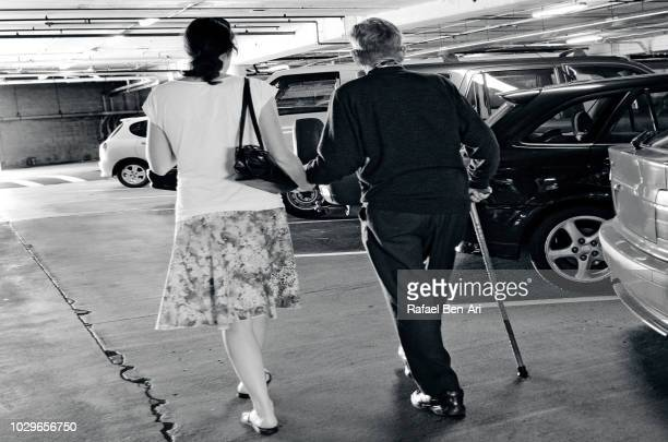 Adult Woman Supporting an Old Man in a Parking Lot