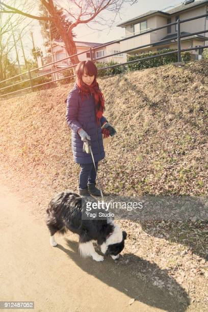 adult woman taking a walk with a dog near river side - black hairy women stock pictures, royalty-free photos & images