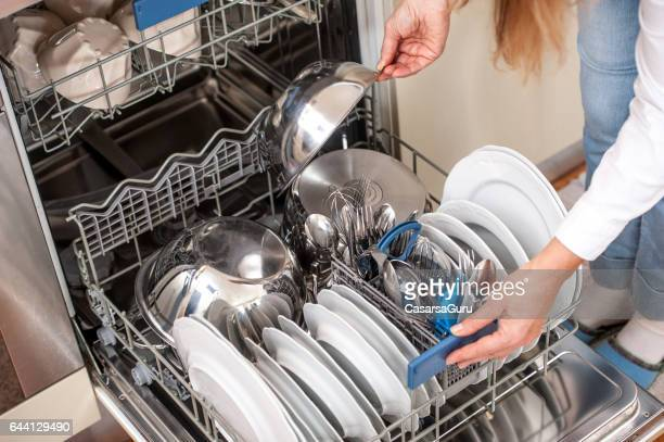 Adult Woman Unloading Dishwasher In The Kitchen