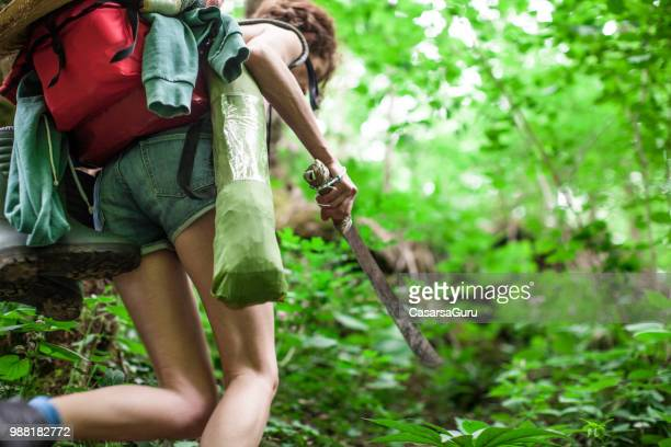 adult woman using machete in forest - machete stock pictures, royalty-free photos & images