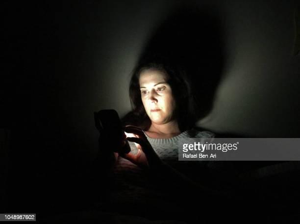 adult woman using smarphone in a dark night - rafael ben ari stock pictures, royalty-free photos & images