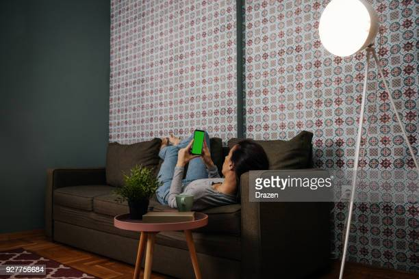 Adult woman using smart home app in automated home