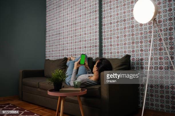 Erwachsene Frau mit smart home app in automatisierten Haus