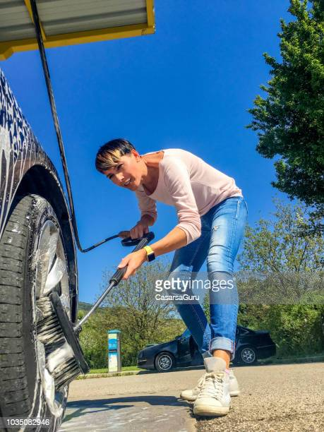 adult woman using washing broom to clean car wheels - car wash brush stock pictures, royalty-free photos & images