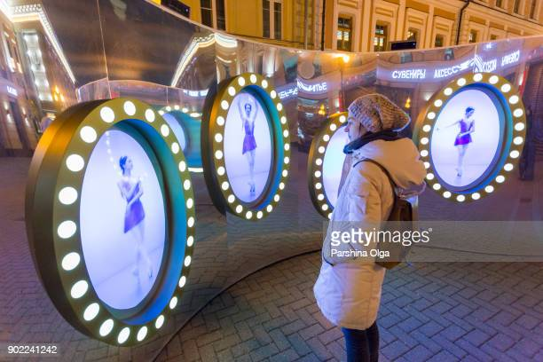 Adult woman watch at Christmas installation on Old Arbat in Moscow