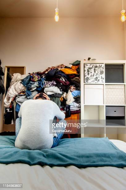 adult woman with a heap of clothes to iron and fold - greed stock pictures, royalty-free photos & images