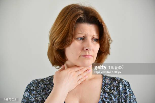 adult woman with a sore throat on light background - faringe fotografías e imágenes de stock