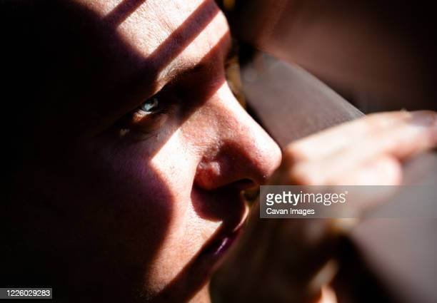 adult woman with blue eyes opening a wooden curtain with her fingers to look through the window while the sunlight creates sun and shadow on her face. horizontal photo. - mujeres de mediana edad fotografías e imágenes de stock