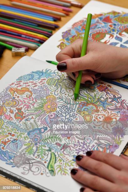 Adult woman with green pencil completing an undersea coloring book on a wood table