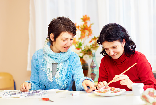 adult woman with special needs are engaged in handcraft in rehabilitation center 858357996