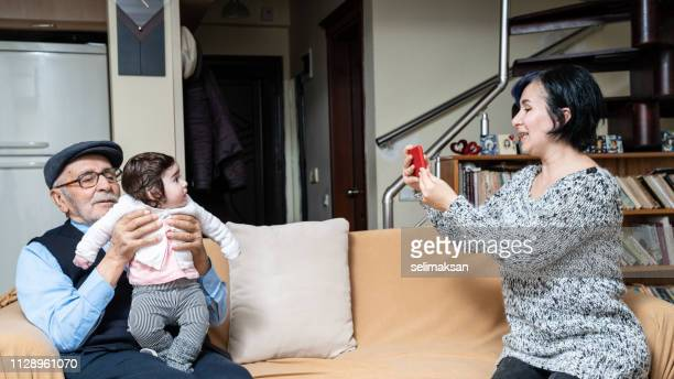 Adult WomanTaking Portrait Of Senior Man Holding Great Granddaughter With Mobile Phone